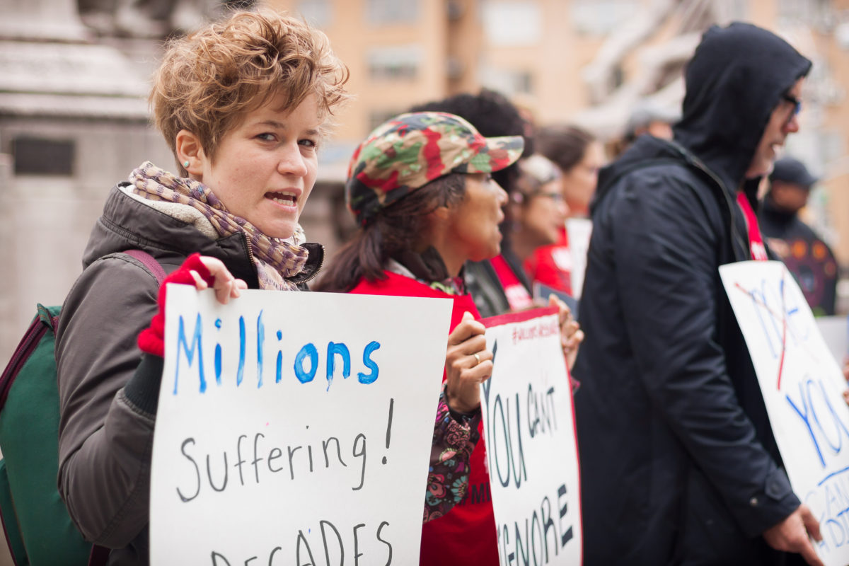 woman in line of protestors holds sign,
